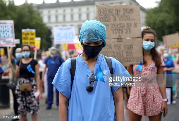 Workers hold a minute's silence to pay tribute to NHS staff who have died with coronavirus during a march through the streets of London on August 8...