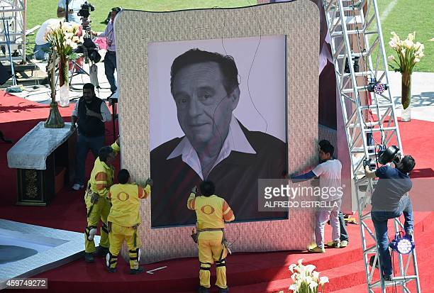 Workers hold a portrait of Mexico's iconic television comedian Roberto Gomez Bolanos before a tribute in his honour two days after his death on...
