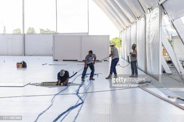 Workers hold a string as part a field hospital being built with private funds at the Athletes' Park in Barra da Tijuca neighborhood on April 29 2020...