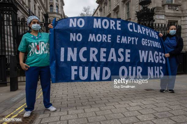 Workers hold banners demanding a pay rise at Downing Street on March 7, 2021 in London, England. The Department of Health and Social Care has come...