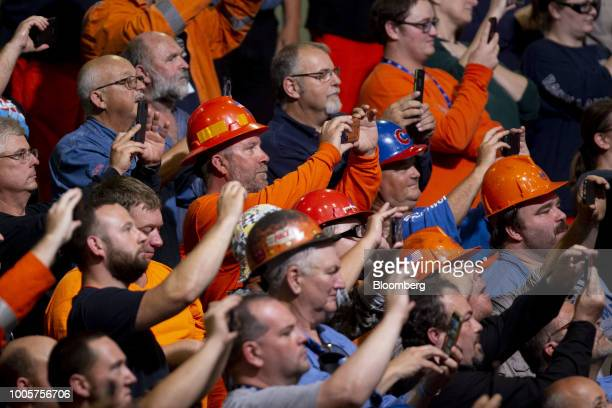 Workers hold mobile phones as they listen to US President Donald Trump speak at the US Steel Corp Granite City Works facility in Granite City...