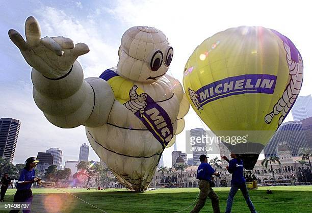Workers hold on to a rope tied to a giant Michelin Man balloon at the Merdeka Square in Kuala Lumpur 14 march 2001 The 16story high Michelin Man or...