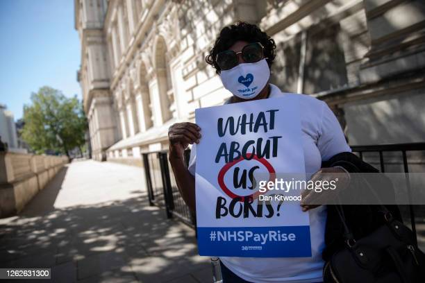 Workers hold placards asking the government for a pay rise outside Downing Street on July 30, 2020 in London, England. The group were to hand in a...