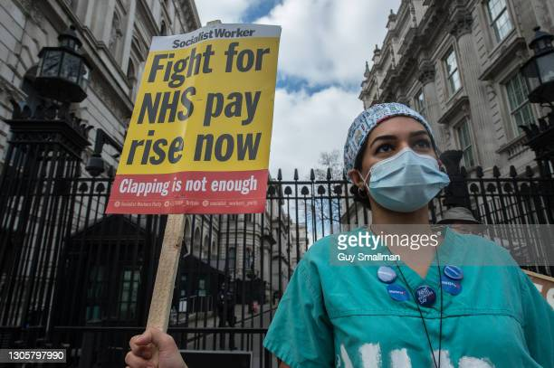 Workers hold placards demanding a pay rise at Downing Street on March 7, 2021 in London, England. The Department of Health and Social Care has come...