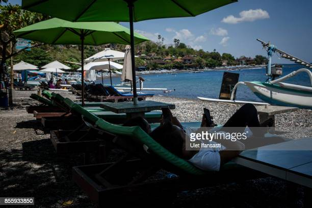 KARANGASEM BALI INDONESIA SEPTEMBER 30 Workers hold smart phone as sit on sun lounger chair as emptied of tourists at Amed beach on September 30 2017...