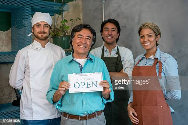 Workers holding an open sign at a restaurant