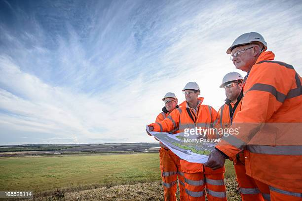 Workers holding plans inspecting land around surface coal mine restoration