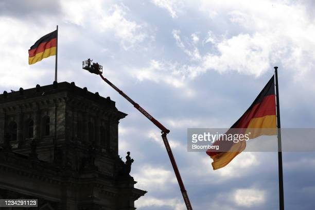Workers in a cherry picker outside the Reichstag building in Berlin, Germany, on Thursday, July 29, 2021. Germany reports gross domestic product...
