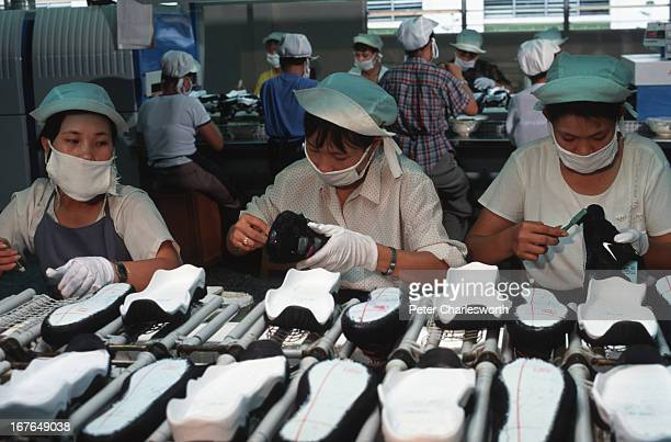 Workers in a Nike factory near Ho Chi Minh City use glue to put together Nike sports shoes on a production line conveyor belt