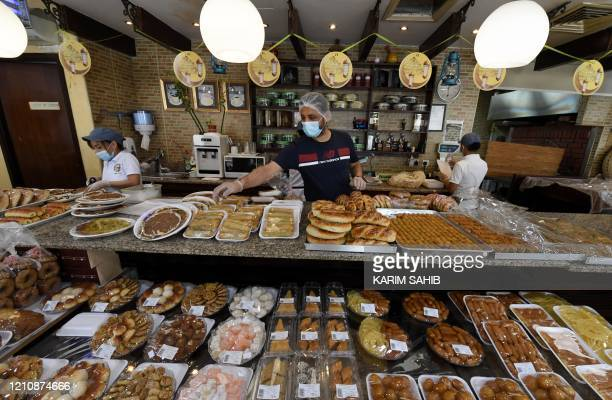 Workers in a pastry shop wearing surgical masks due to the COVID19 coronavirus pandemic prepare food for customers in Dubai on the first day of the...