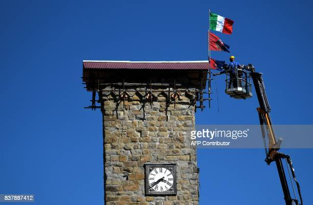 Workers in an aerial bucket put flags on top of a clock tower in Amatrice on August 23 2017 a year after a deadly earthquake left nearly 300 people...