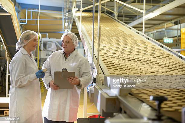 Workers in biscuit factory discuss production next to conveyor of freshly made biscuits