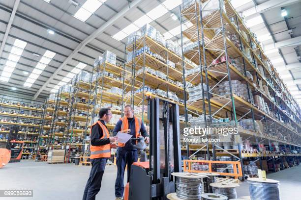 Workers in cable store warehouse at cable storage facility