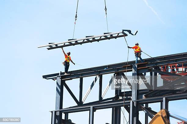 Workers in construction industry, cranes