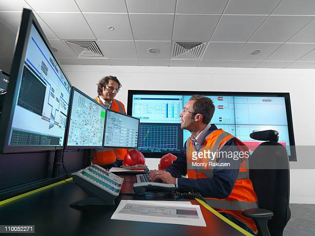 Workers in control room with screens