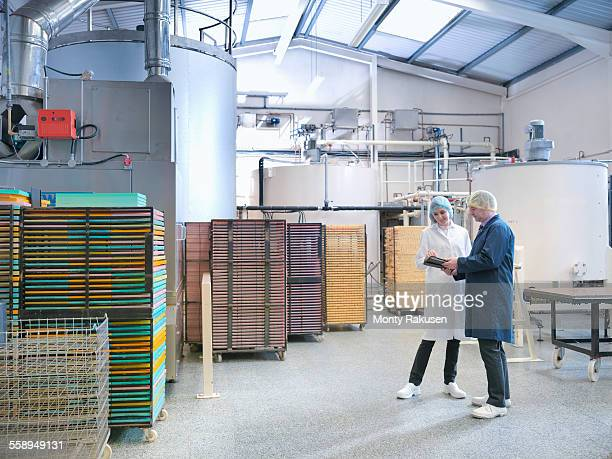 workers in discussion by storage tanks in chocolate factory - candy factory stock pictures, royalty-free photos & images