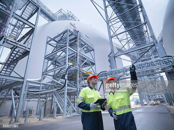 Workers in discussion in biomass facility, low angle view