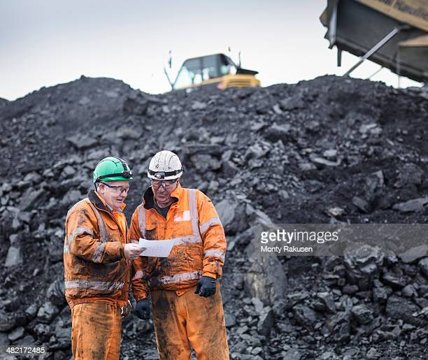 workers in discussion in front of coal stocks in surface coal mine - coal mining stock photos and pictures