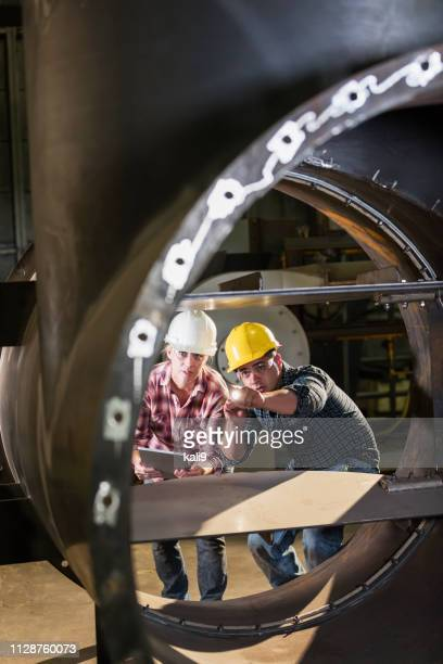 workers in factory inspecting metal object - metallic look stock pictures, royalty-free photos & images