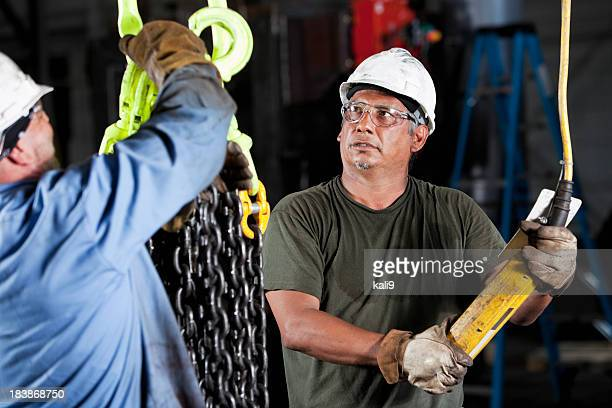 Arbeiter in der Fabrik mit den industriellen Haken-und-Ketten