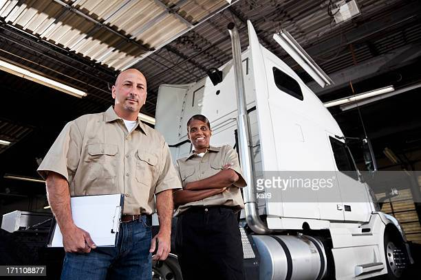 Workers in garage with semi-truck