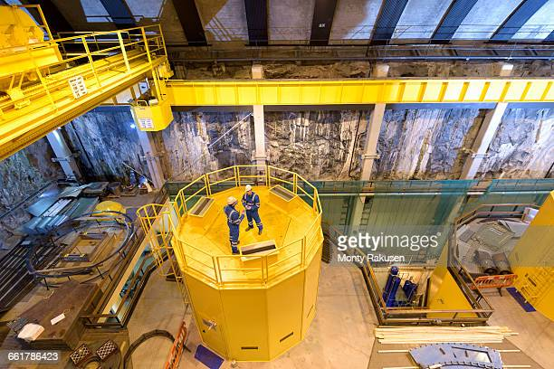 workers in generating hall in hydroelectric power station, high angle view - monty rakusen stock photos and pictures