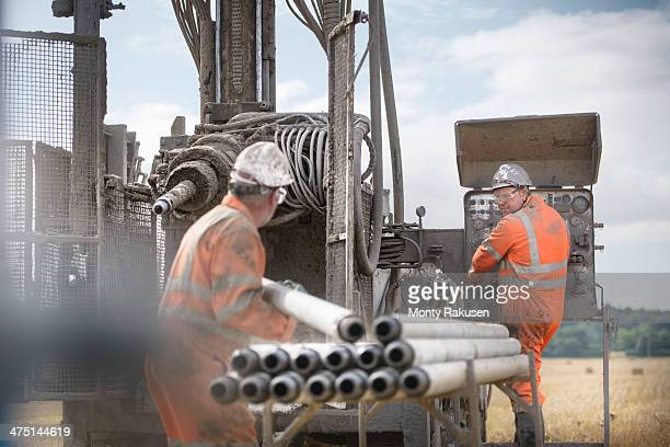 Workers in hard hats operating drilling rig