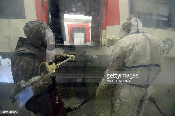 Workers in hermetic kevlar gear remove the asbestos from former carriages of the Paris RER regional express railway line at the Veolia utility group...