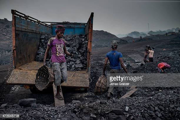Workers in Jharia are loading a truck with coal using baskets that they carry on top of their heads Jharia in India's eastern Jharkand state is...