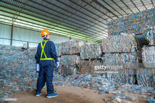 workers in landfill dumping, garbage engineer, recycling, wearing a safety suit standing in the recycling center have a plastic bottle for recycling in the factory. - plastic stockfoto's en -beelden