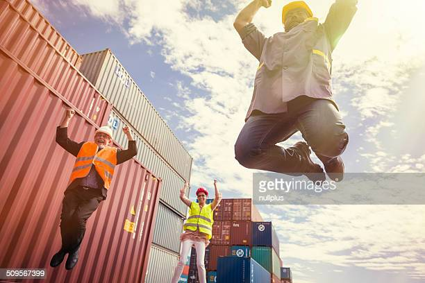 workers in large container port, jumping for joy