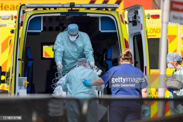 Workers in PPE take a patient with an unknown condition from an ambulance at St Thomas' Hospital on April 10, 2020 in London, England. Public Easter...