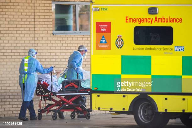 NHS workers in PPE take a patient with an unknown condition to an ambulance at Queens Hospital on April 21 2020 in London England The British...
