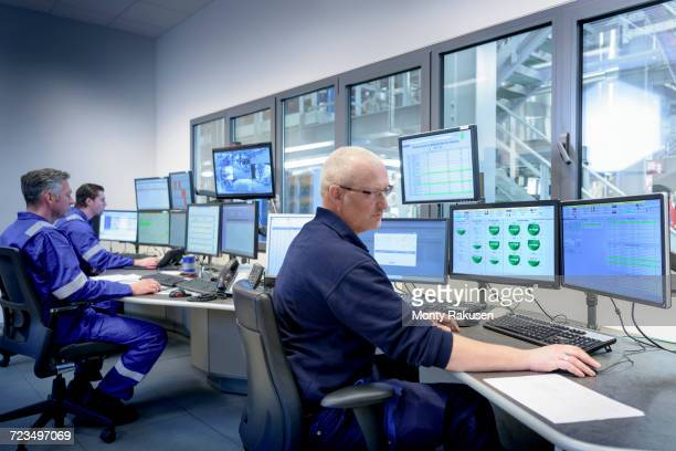Workers in process control room in oil blending factory