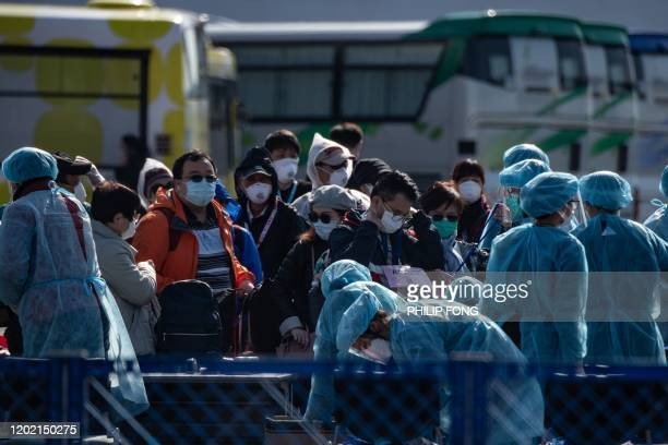 Workers in protective clothes measures the body temperature of a passenger disembarking from the Diamond Princess cruise ship in quarantine due to...