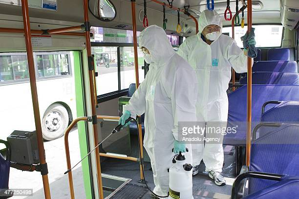 Workers in protective gear against the Middle East Respiratory Syndrome virus sanitize a public bus at a transport company depot on June 15 2015 in...
