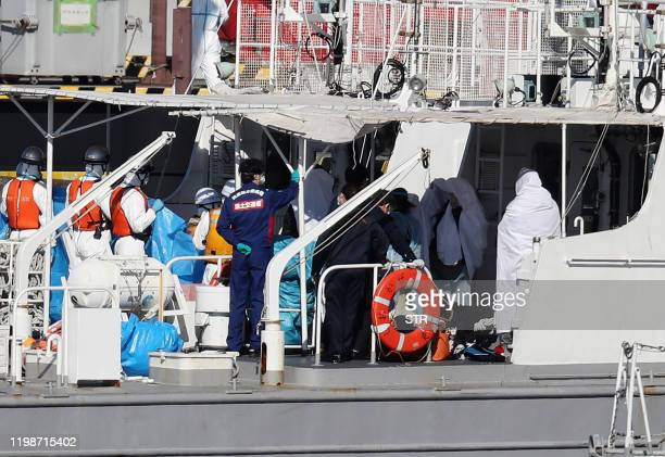 Workers in protective gear on board a Japan Coast Guard boat transfer people wrapped in white sheets from the Diamond Princess cruise ship in...