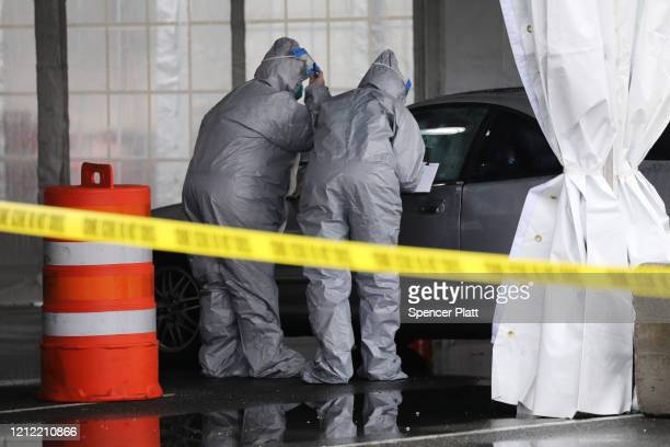 Workers in protective gear operate a drive through COVID19 mobile testing center on March 13 2020 in New Rochelle New York The center serves all...