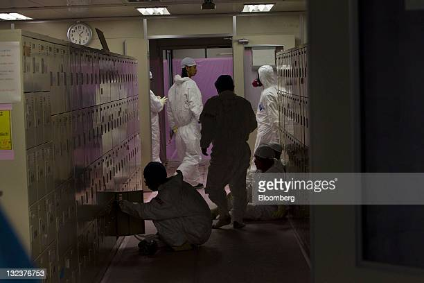 Workers in protective suits gather near their lockers inside the emergency operation center at the crippled Tokyo Electric Power Co Fukushima DaiIchi...