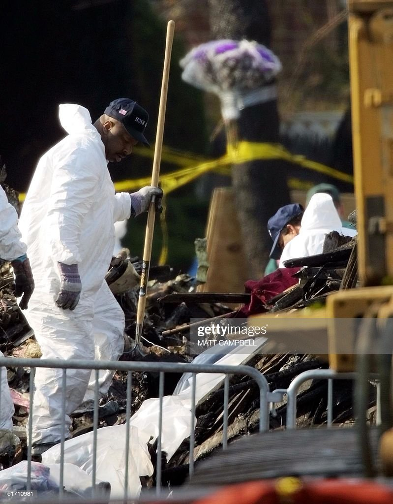 Workers in protective suits sift through debris fr : News Photo