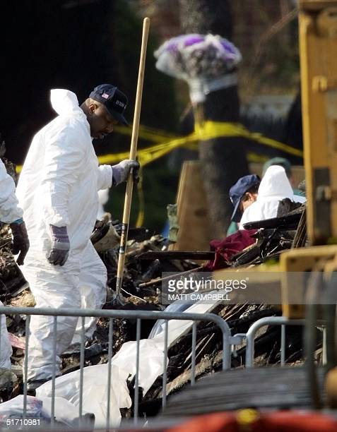 Workers in protective suits sift through debris from the crash of America Airlines Flight 587 15 November 2001 in Queens New York Experts...