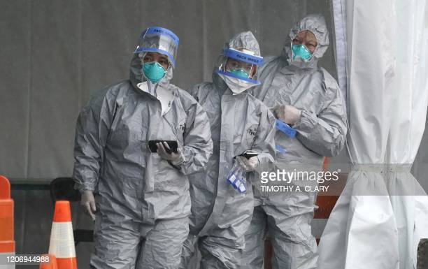 Workers in protective suits wait for people to be tested for Coronavirus as they arrive by car at the State's First Drive Through COVID19 Mobile...