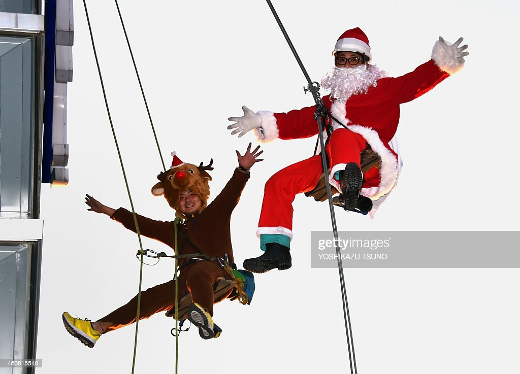 Workers in Santa Claus (R) and reindeer (L) costumes are pictured as they clean windows outside a shopping mall along Tokyo's waterfront on December 24, 2014. The costumes were worn as part of a Christmas promotional event to attract shoppers. AFP PHOTO / Yoshikazu TSUNO