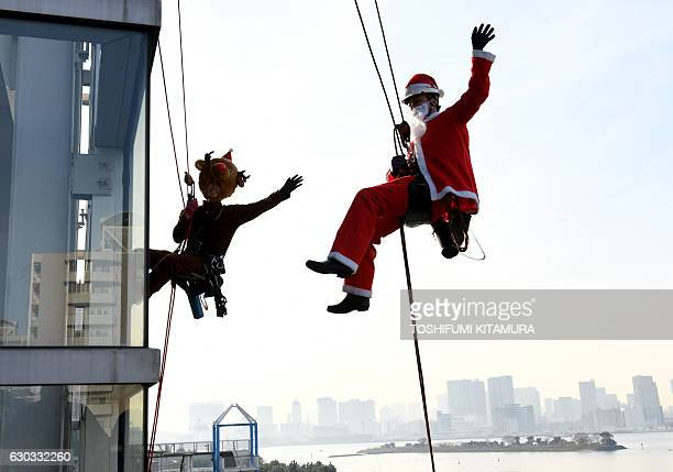 Workers in Santa Claus and reindeer costumes wave while cleaning windows outside the 'Decks Tokyo Beach' shopping mall along Tokyo's waterfront on...