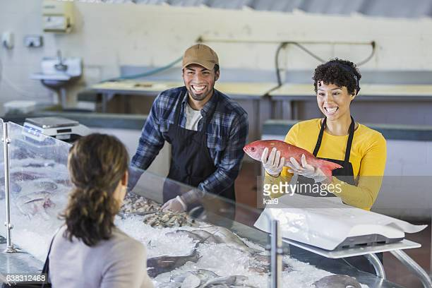 Workers in seafood market helping customer