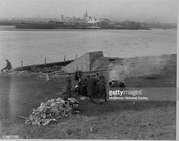 Workers in St. Paul eat lunch beside the Mississippi River. Minnesota, November 12th, 1935