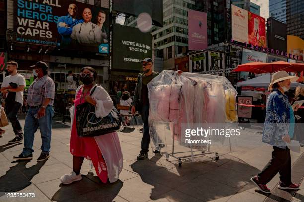 Workers in the fashion industry push a cart of dresses through the Times Square neighborhood of New York, U.S., on Saturday, Sept. 4, 2021. This...