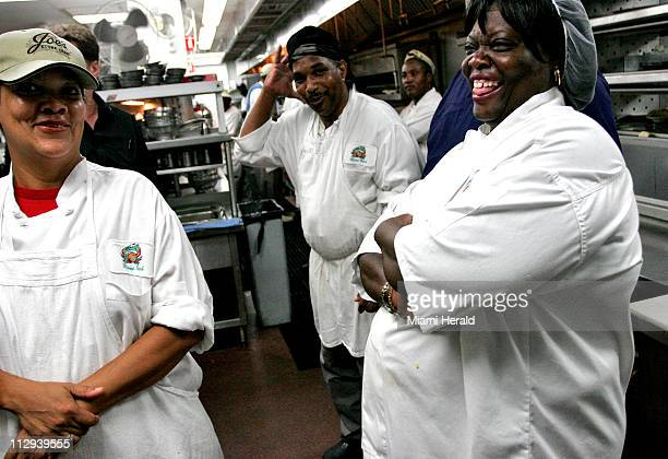 Workers in the kitchen at Joe's Stone Crab Restaurant watch the media enter a few moments after President George W Bush arrived for a dinner with...