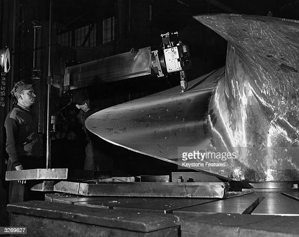 Workers in the machine shop of US Steel's Federal shipyard at Kearny New Jersey operating machinery making a rough cut on the blade of a ship...