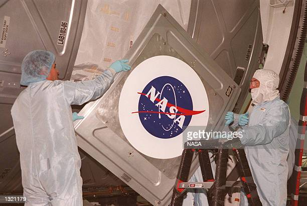 Workers in the Space Station Processing Facility place the NASA logo on the US Laboratory Destiny the key US element of the International Space...
